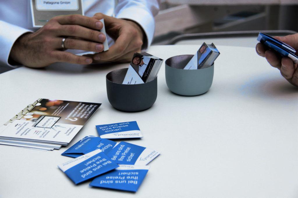 Das Patagona-Messeteam hält Visitenkarten und Giveaways zum Austausch über den Pricemonitor bereit.